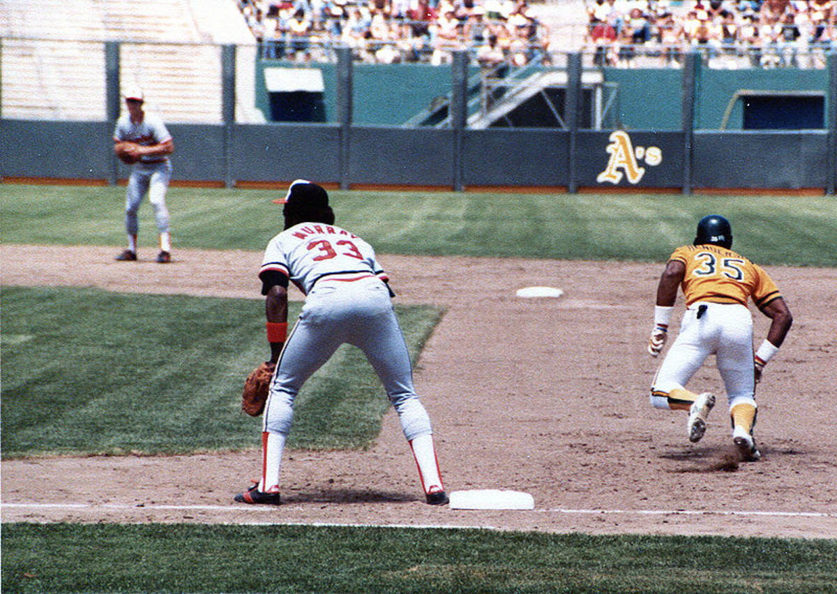 Rickey Henderson takes off for second base as Eddie Murray covers first.  Note Cal Ripken at shortstop in the background.  All three are in baseball's Hall of Fame.