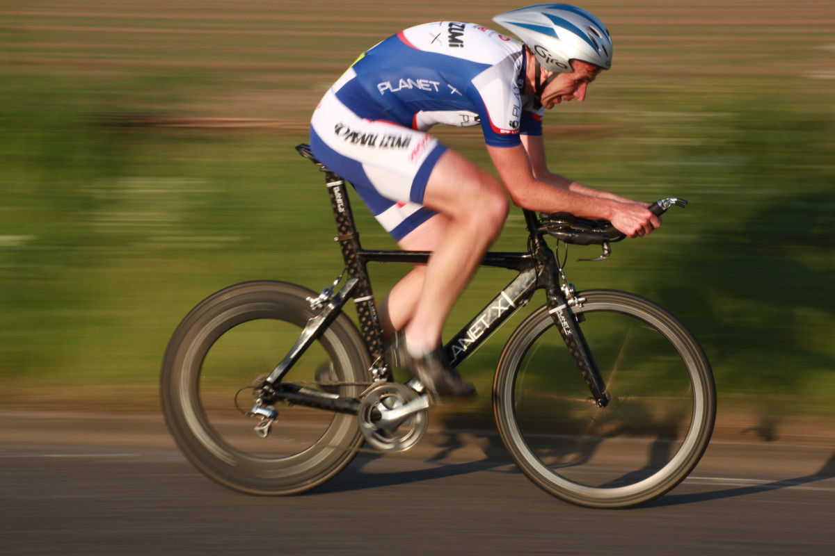 A cyclist competing in a Time Trial on a specific time trial bicycle- A Planet X Stealth with deep section Planet X carbon wheels.
