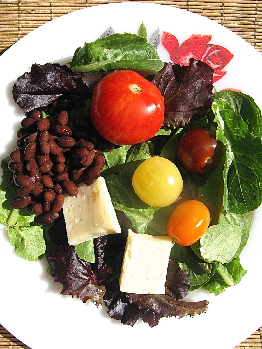 A healthy salad for lunch, with romaine lettuce, beans, tomatoes of different colours, and low fat cheese