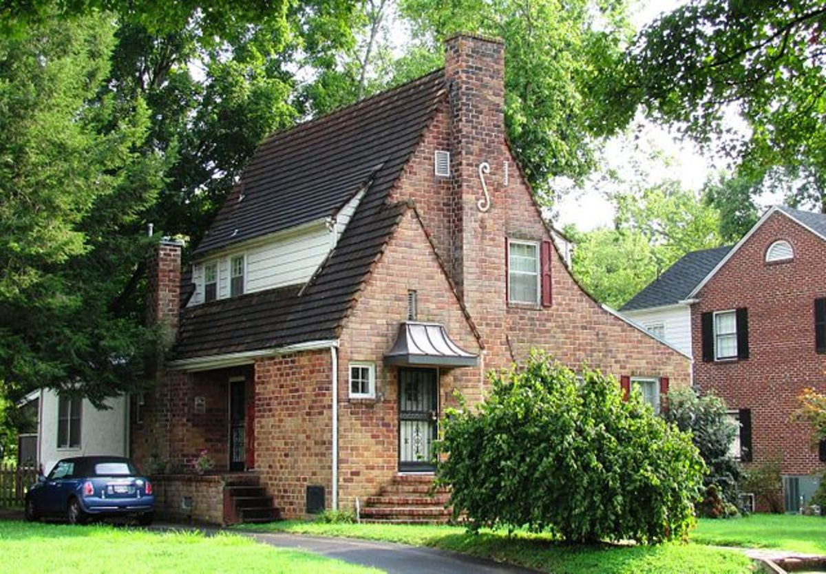 Tudor revival home with brick siding and steep pitched roof.