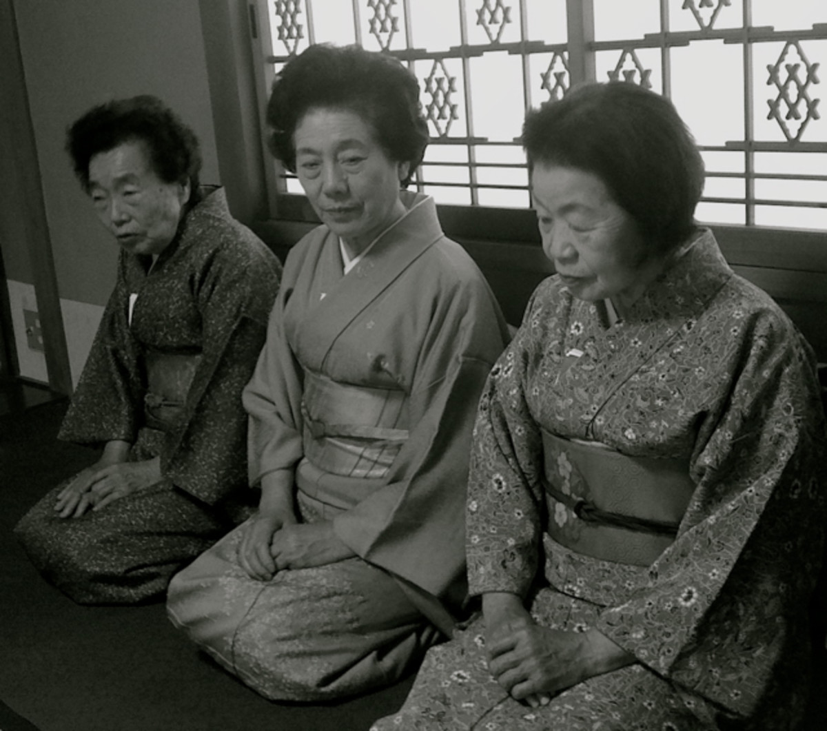 Elderly ladies learn how to prepare tea during a Japanese tea ceremony workshop.