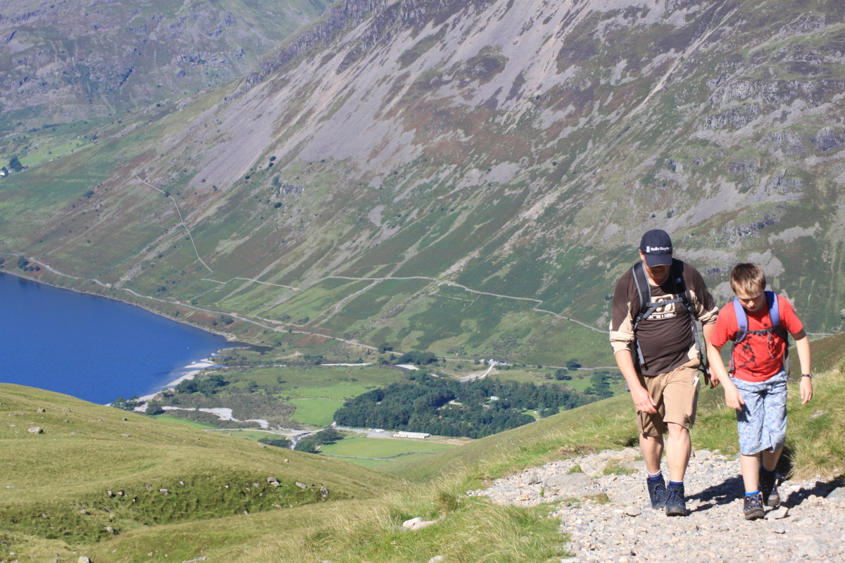 A father and son climbing up the trail towards the summit of Scafell Pike with the deep blue Wast Water and Wasdale in the distance