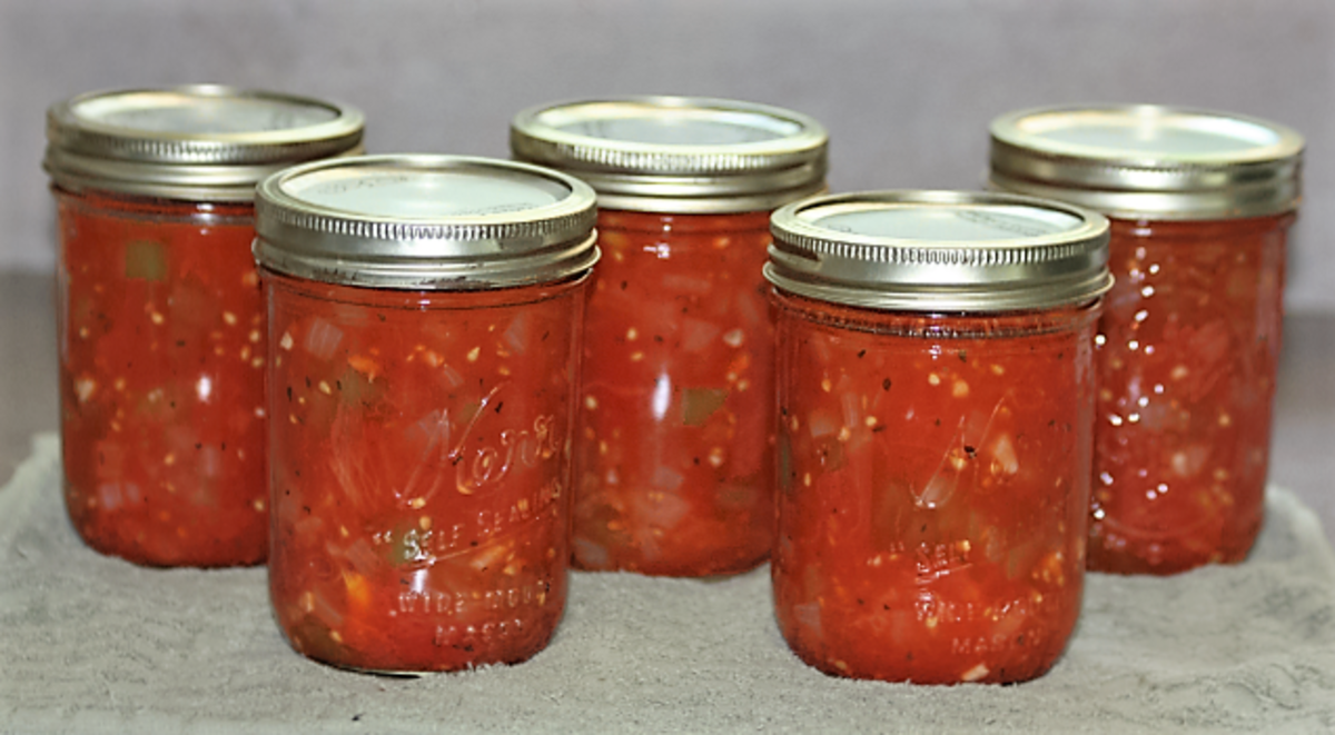 Homemade jars of stewed tomatoes cooling off.