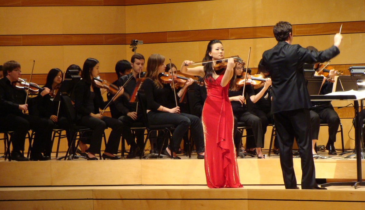The solo violinist and the orchestra create harmony and contrast.