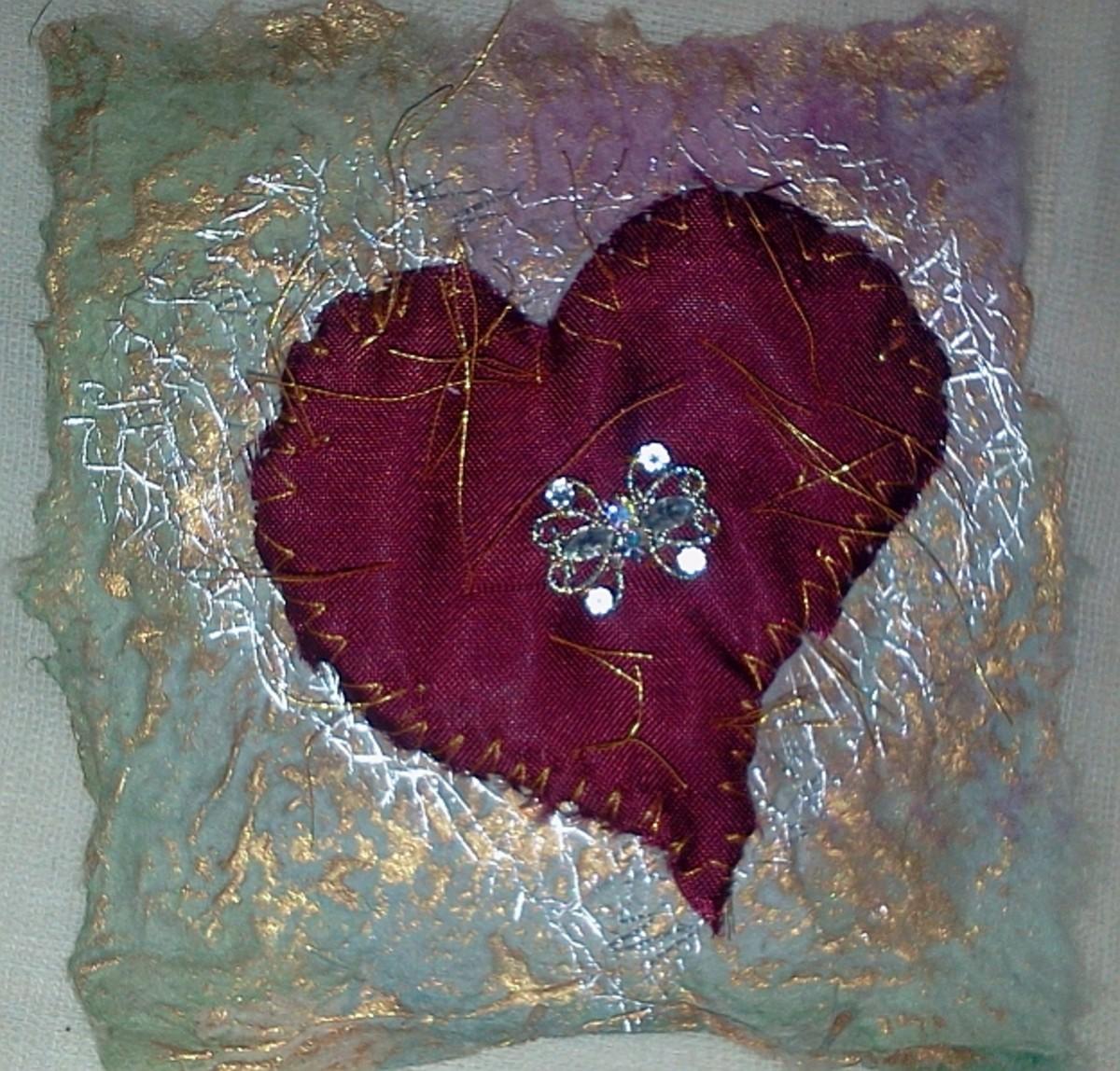 Silk and netting scraps sewn onto handmade paper.