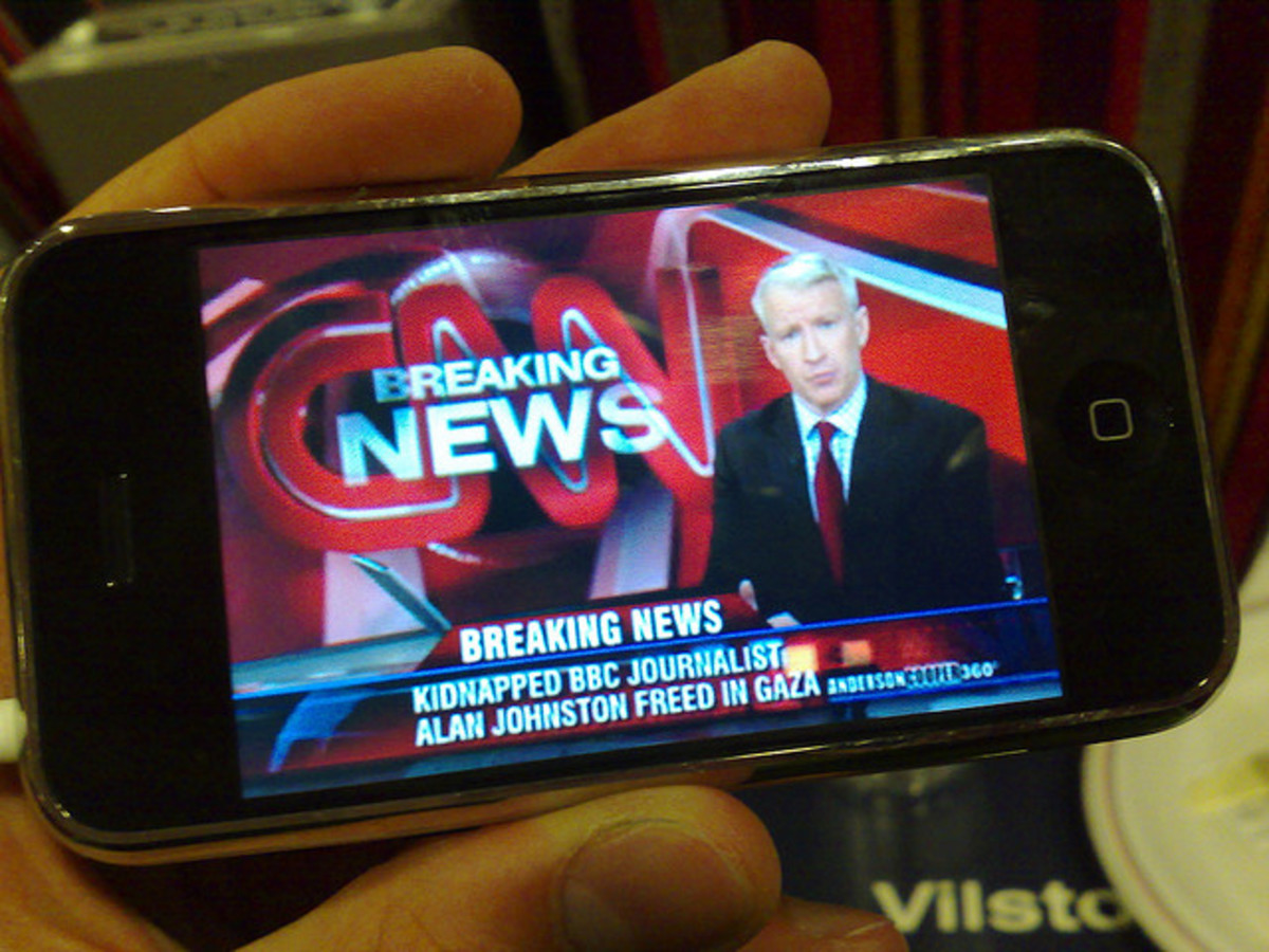 An iconic image of a breaking news broadcast is displayed on the smartphone.