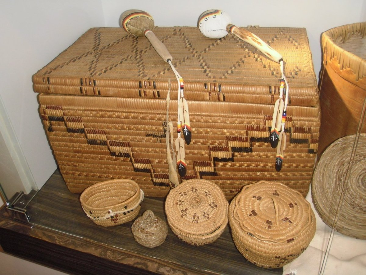 These interior Salish baskets are woven from pine needles, in front, and split cedar root decorated with darker cherry bark, rear.  The collection is displayed in the House of Learning at Thompson Rivers University, Kamloops.