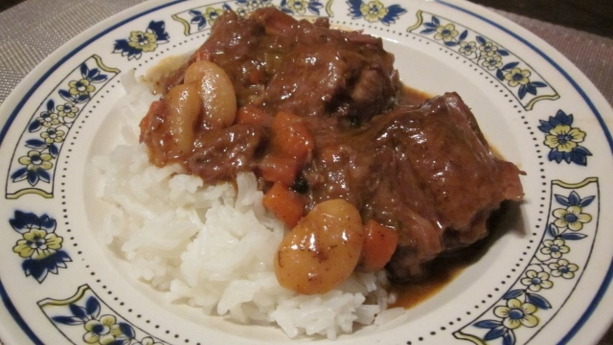 A bowl of steaming hot Jamaican-style oxtail stew served over fluffy white rice is a flavorful taste of the Caribbean.