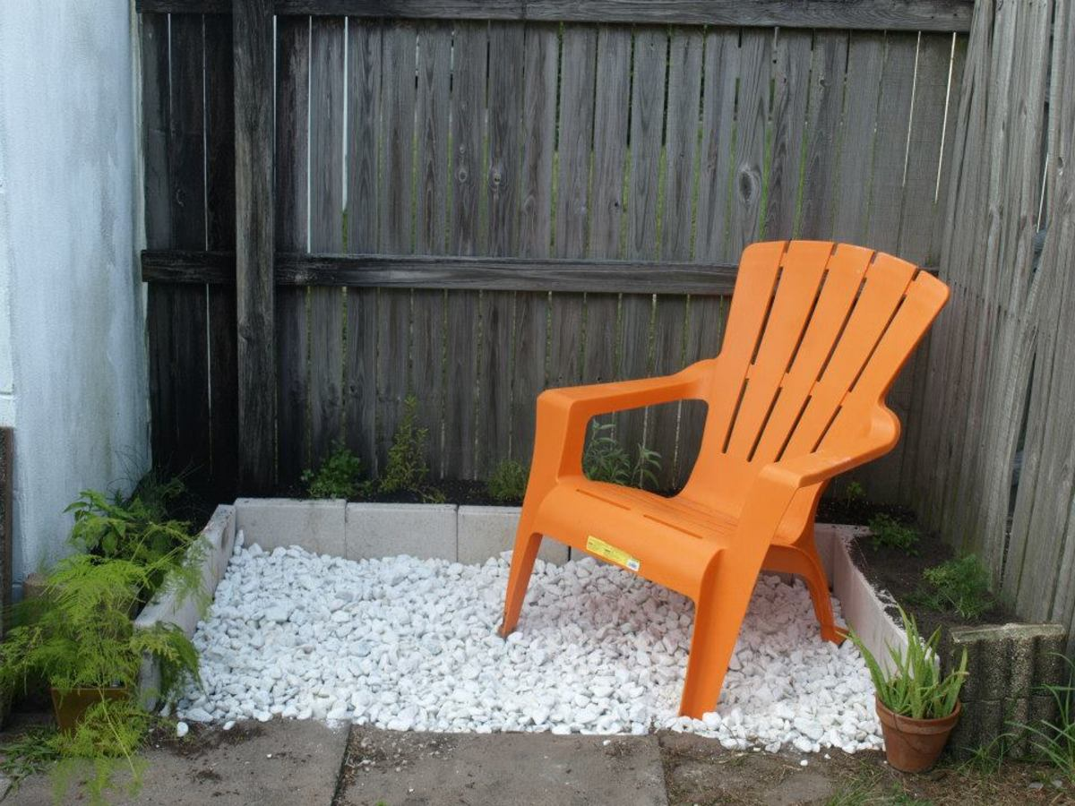With the addition of marble chips and the Adirondack chair—a little color in orange—the herb garden is complete and ready for a relaxing morning cup of coffee.