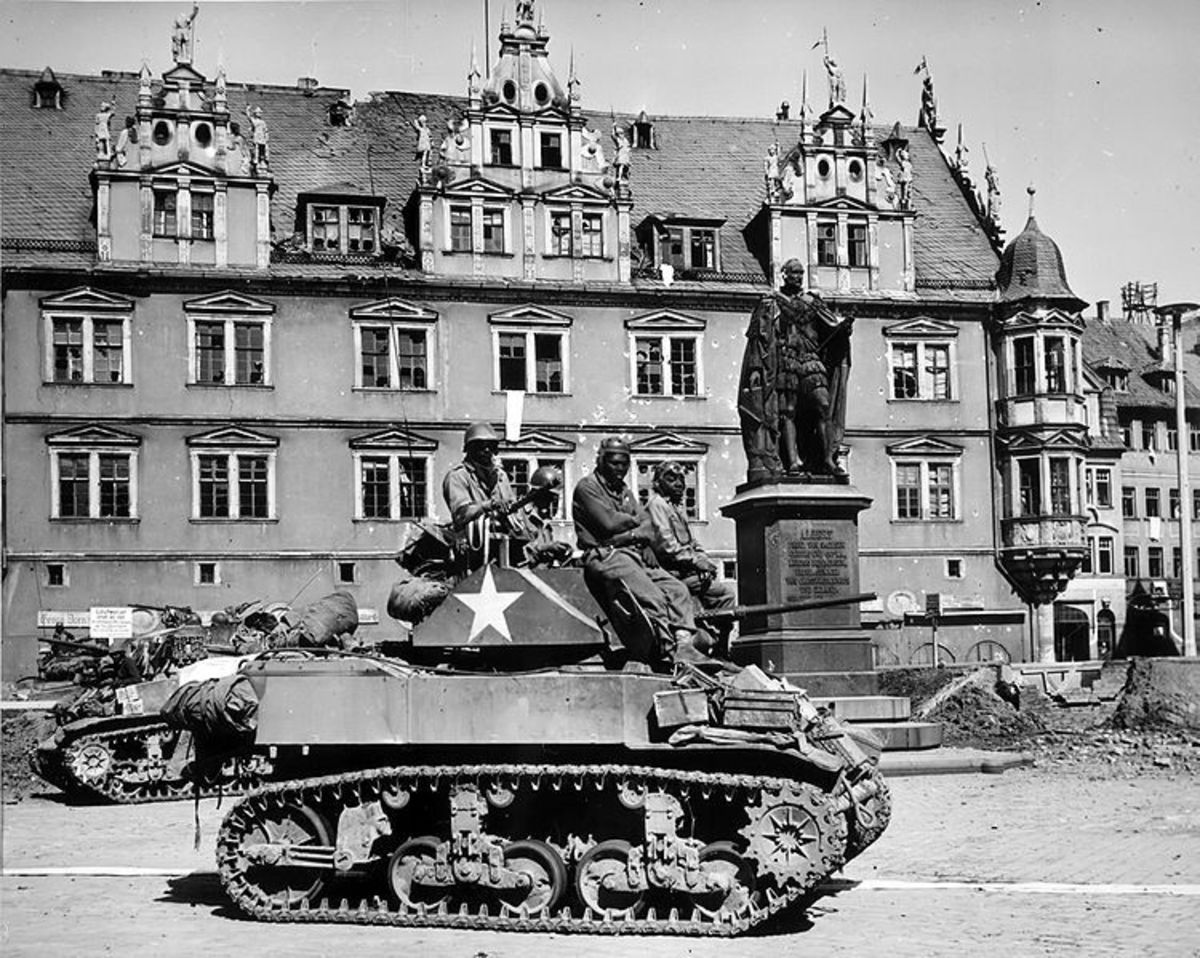 Members of Company D, 761st Tank Battalion (Black Panthers) awaiting orders in their M5 Stuart light tank to clear out German machine gun nests in Coburg, Germany. April 25, 1945.