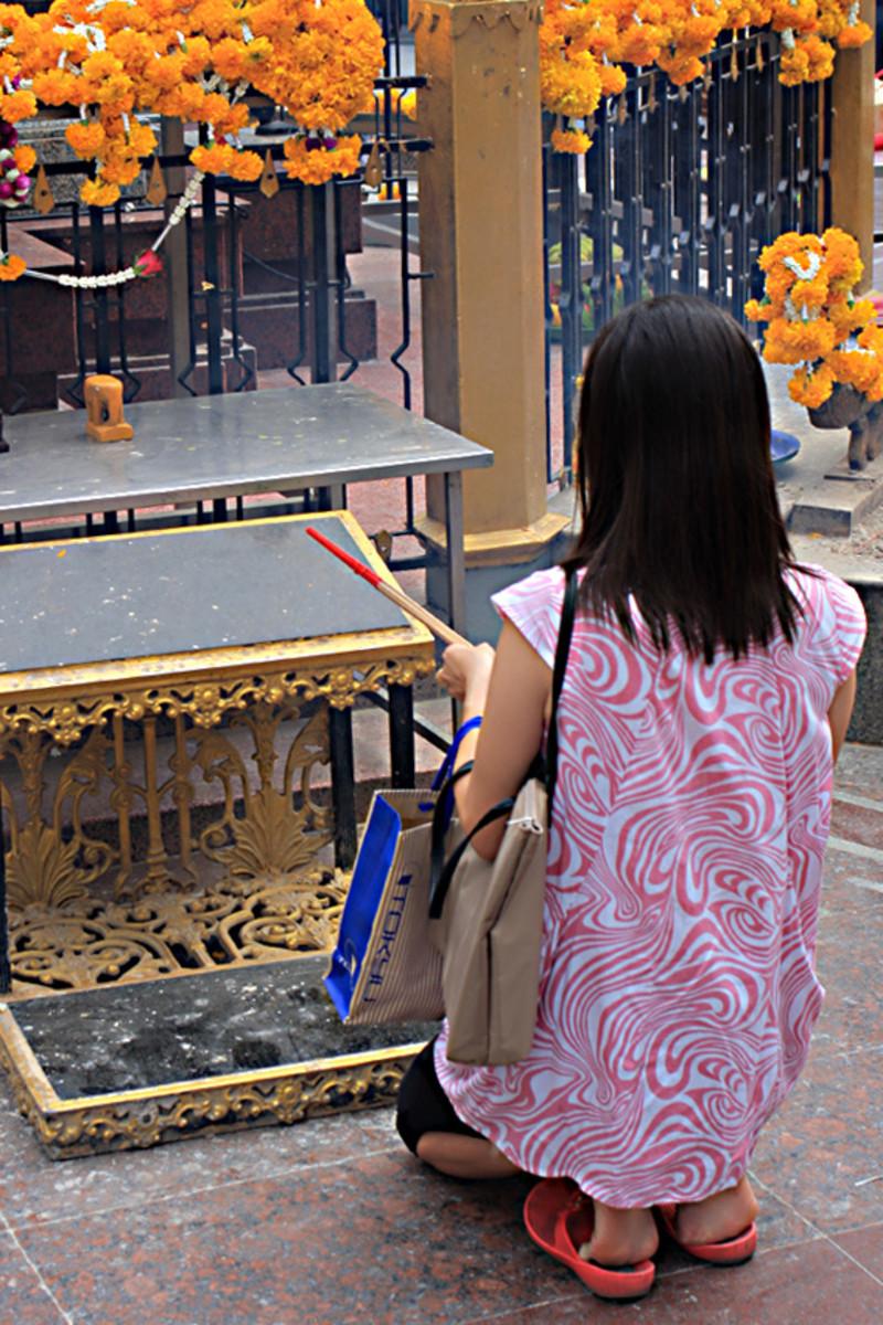 A young girl kneels before the Erawan Shrine