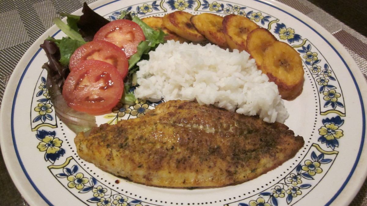 Curry catfish with white rice, fried plantain, fresh spring mix salad and plum tomato slices.