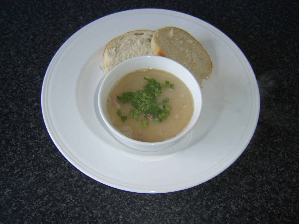 Navy bean and ham soup, garnished with fresh parsley and served with crusty bread.
