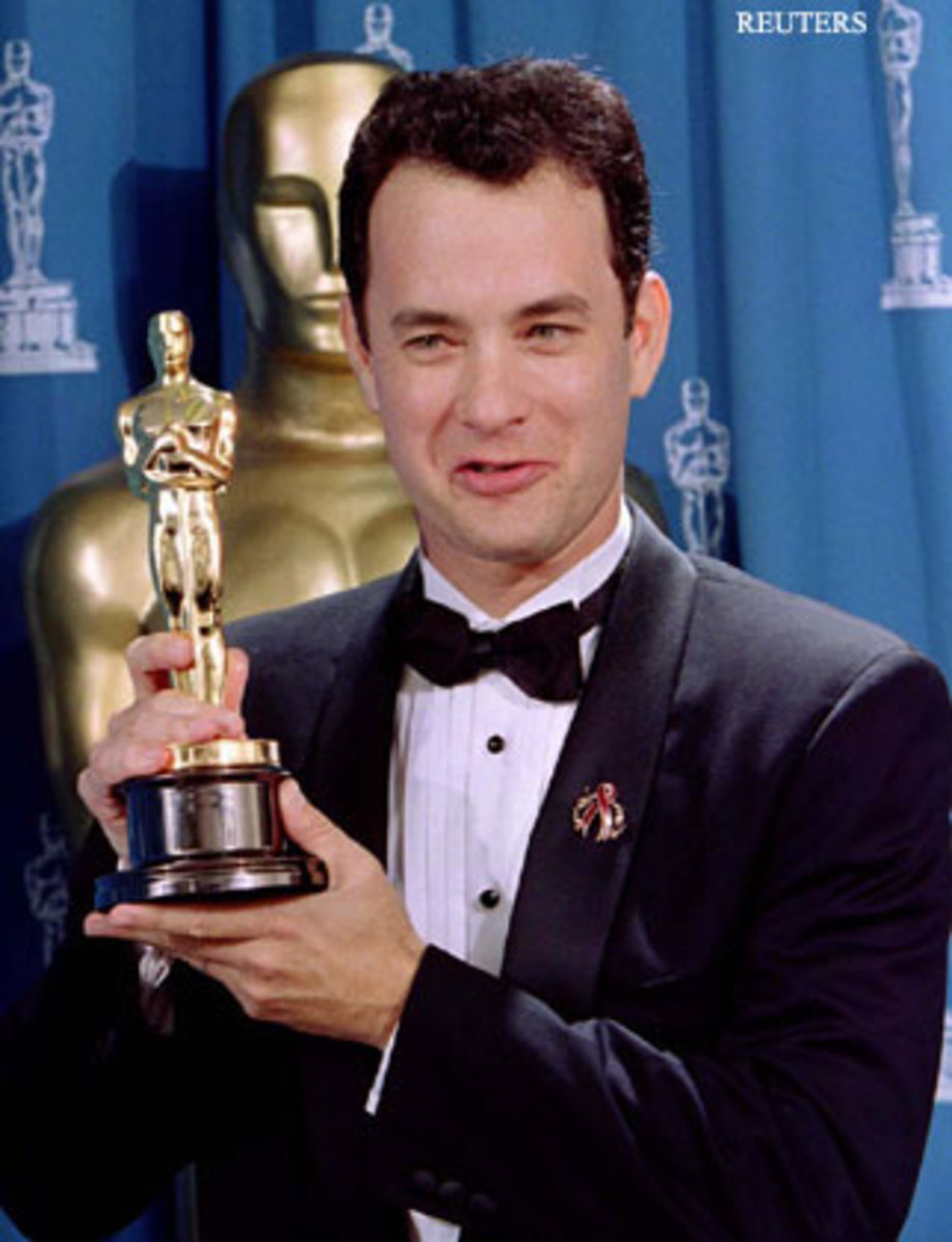 Tom Hanks holding onto his Oscar for his role in Philadelphia.