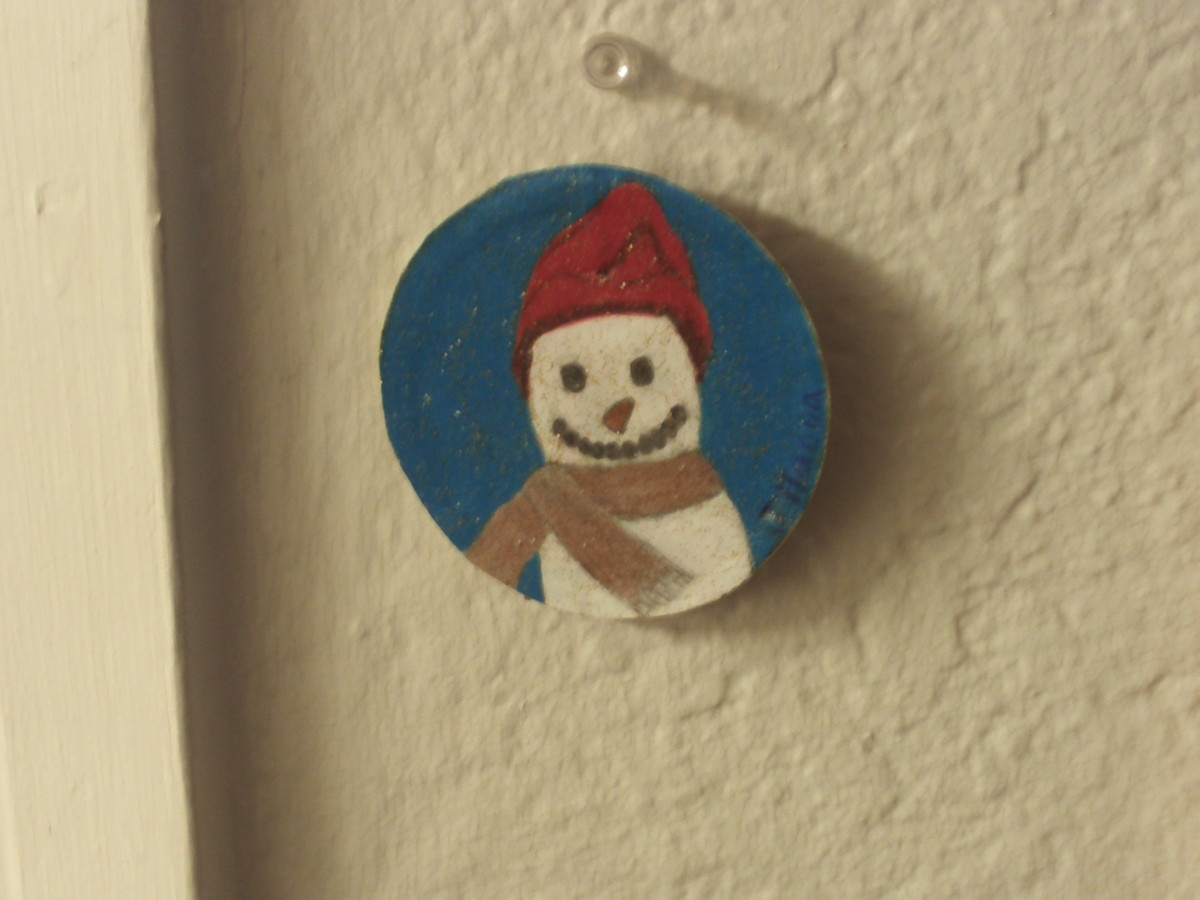It is easy to make a cute snowman ornament out of a canning jar lid.
