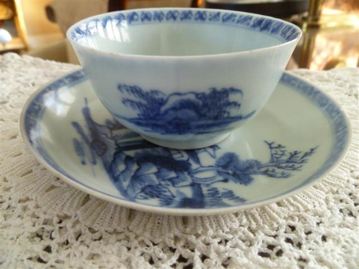 "A teabowl and saucer in the ""Pagoda Riverscape"" pattern."