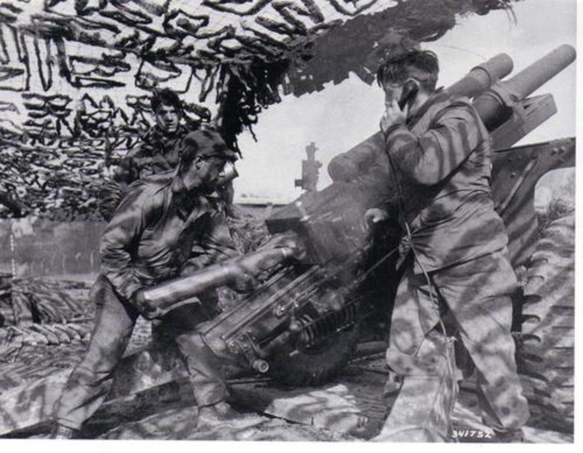 A 105mm howtizer crew preparing to fire (28th ID). The gunner corporal, who operates the quadrant (scope measuring deflection), stands to the left.