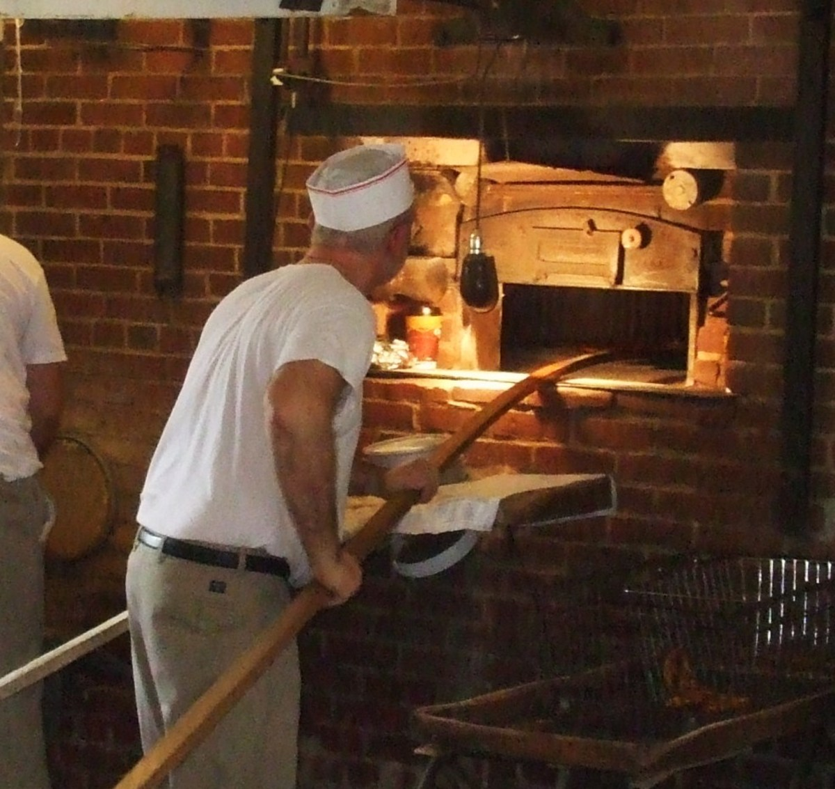 Using a peel to put pretzels into the brick oven at Shuey's Pretzels, Lebanon, PA.