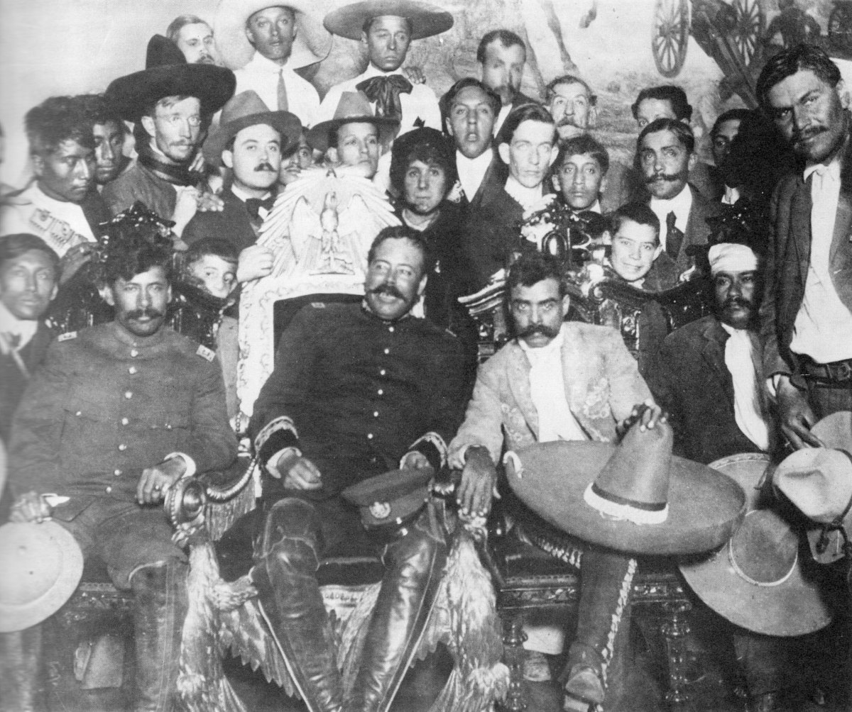 Pancho Villa (in the Presidential chair) chats with Emiliano Zapata at Mexico City. Tómas Urbina is seated at far left, Otilio Montaño (with his head bandaged) is seated to the far right.