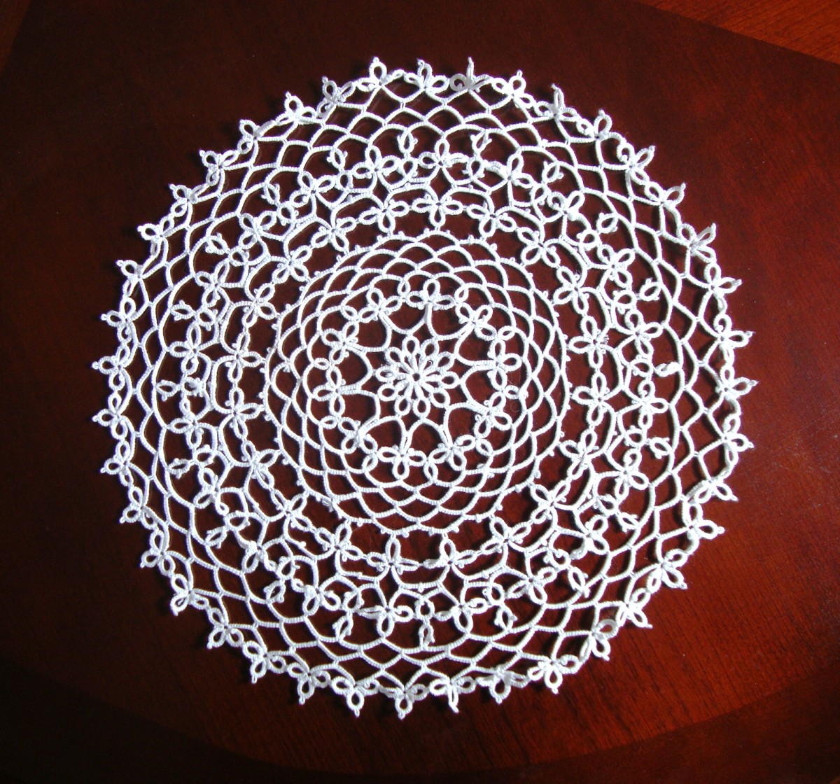 A tatted doily I found in a second-hand store. An experienced doily maker, I knew that it hadn't been done with crochet. I soon learned that this type of doily was produced through tatting. It now lives in my china cabinet.