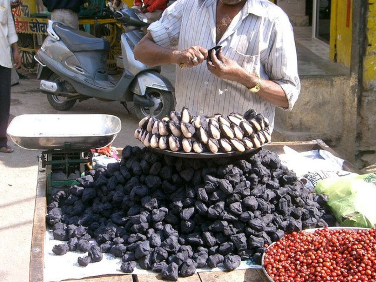 Singhara is a black-colored fruit with a white seed, as seen in this photograph.