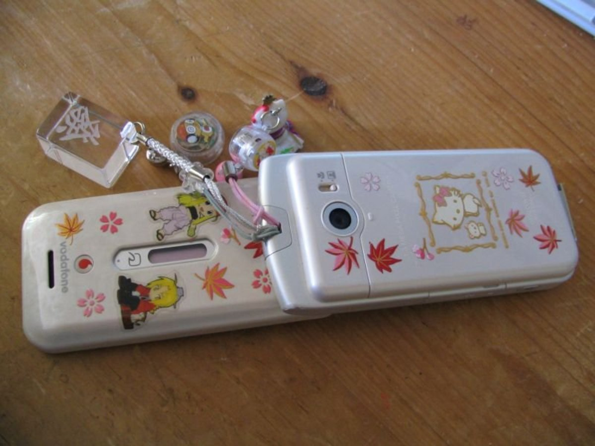 A 2000s-era Japanese cell phone decorated with Maki-e stickers and several different cell phone charms.