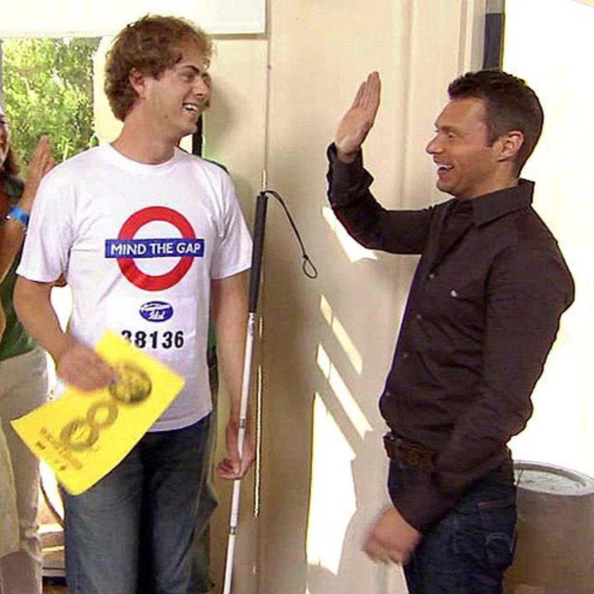 Ryan Seacrest attempts to high-five Scott MacIntyre during American Idol's 8th season.