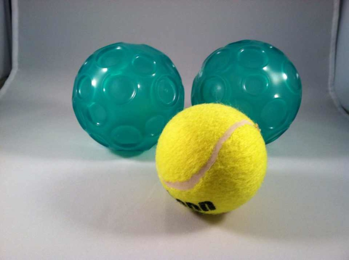 Types of balls for self-massage (textured Franklin balls in back, tennis ball in front).