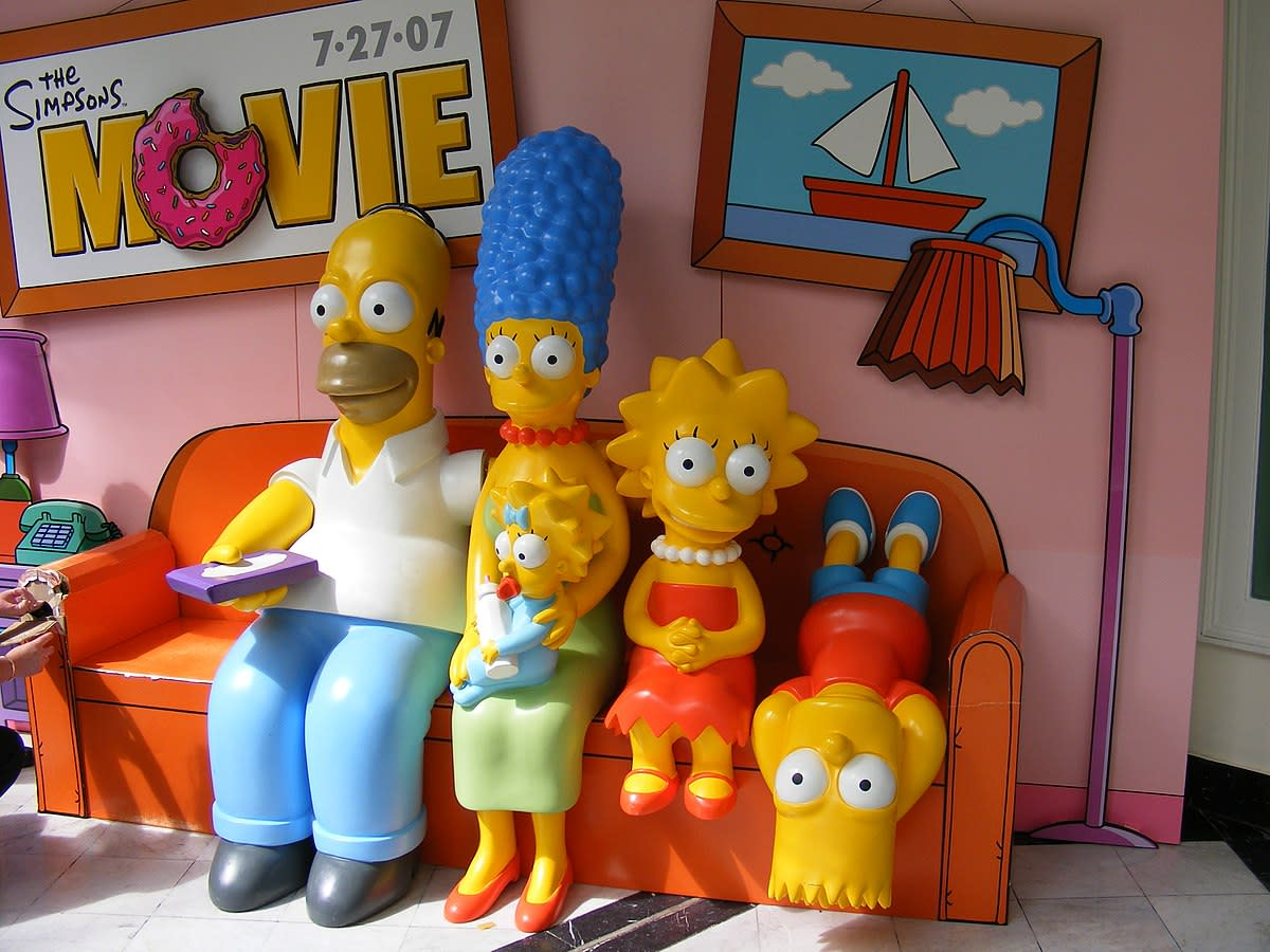 The Simpson family on their couch: Homer, Marge with baby Maggie, Lisa, and Bart.