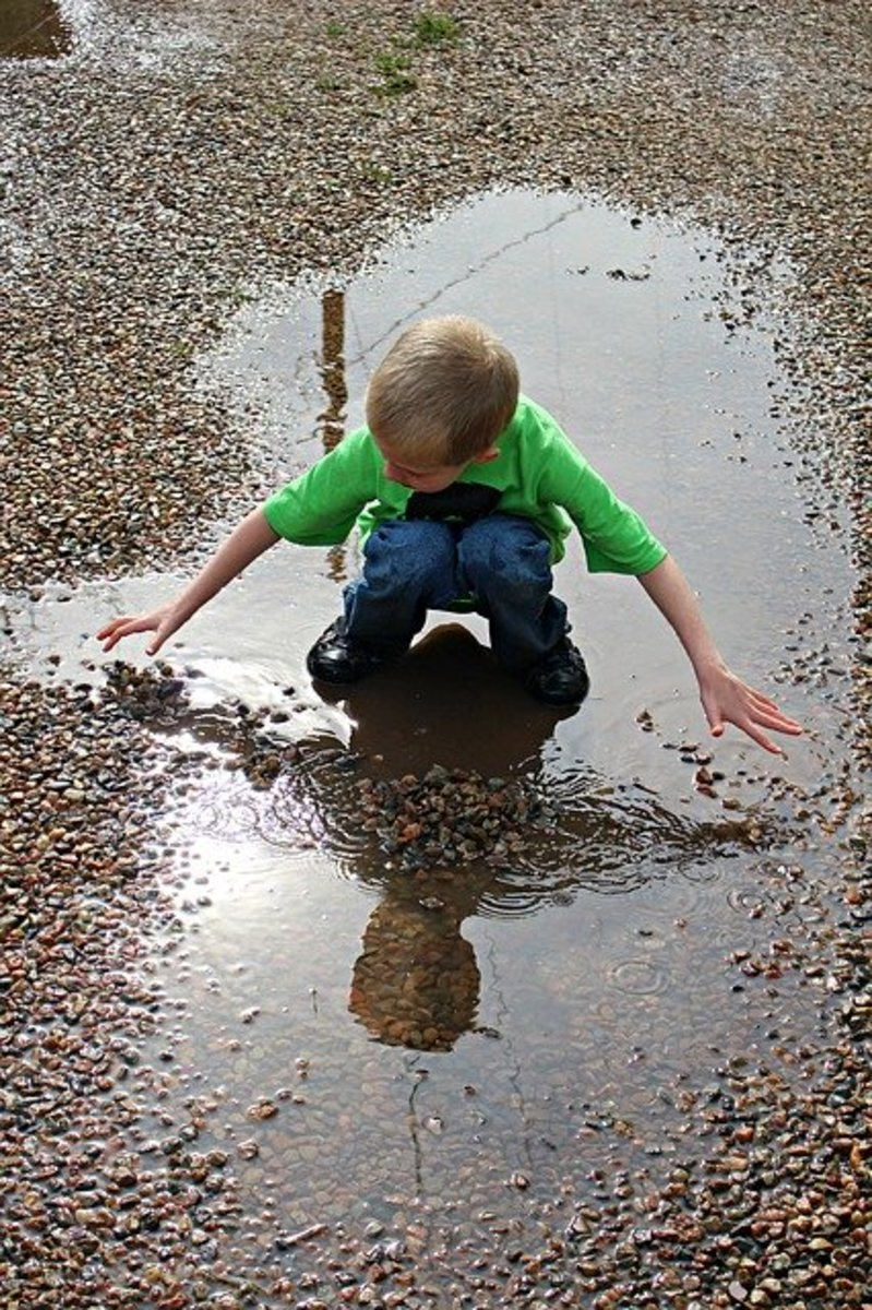 A young boy rapt as he plays in a shining puddle of fresh rain water.