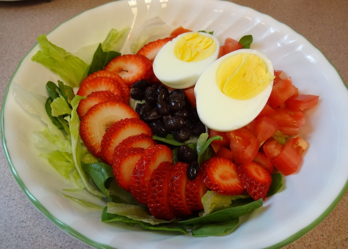 Boiled egg, sliced strawberries, black beans, chopped tomatoes, organic spinach and Iceberg lettuce waiting for the dressing