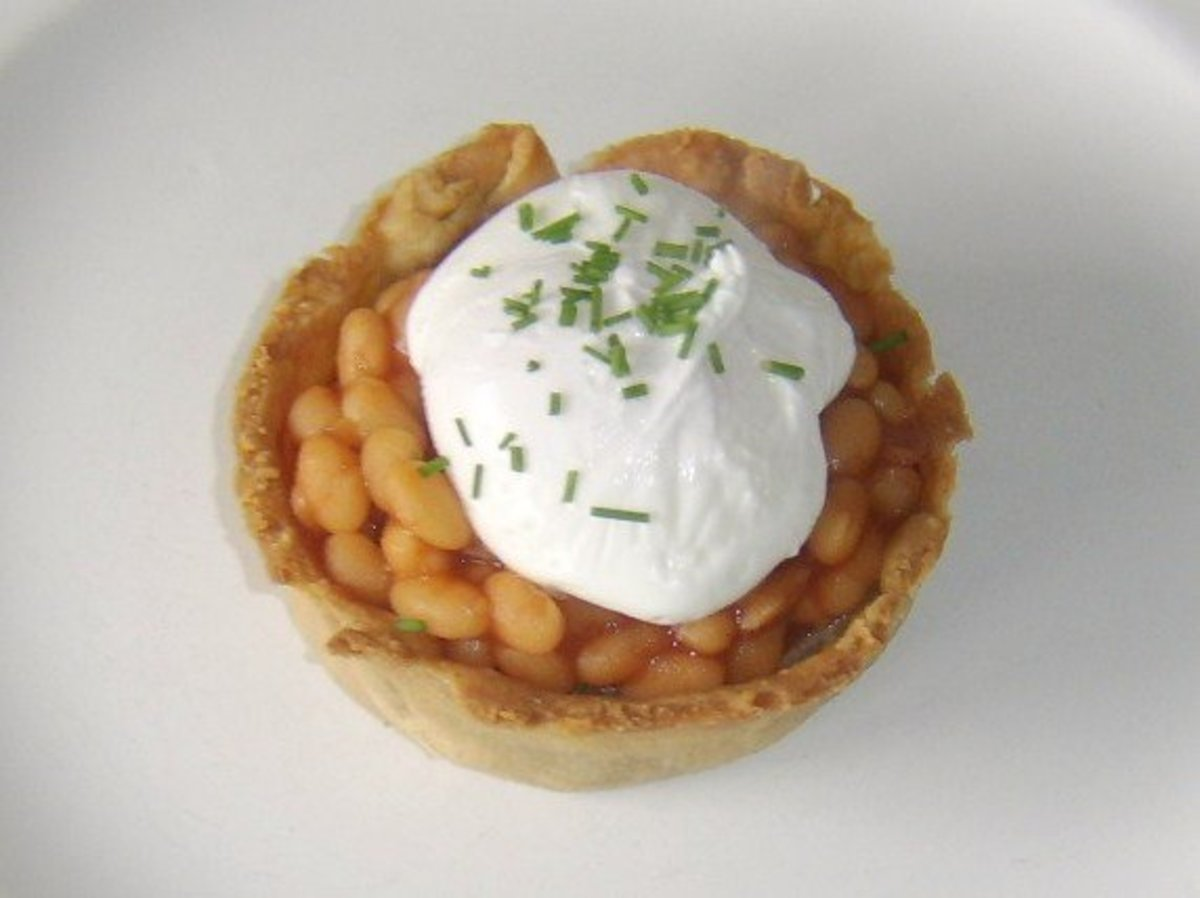 A homemade Scotch pie topped with baked beans in tomato sauce, a poached egg and some freshly chopped chives