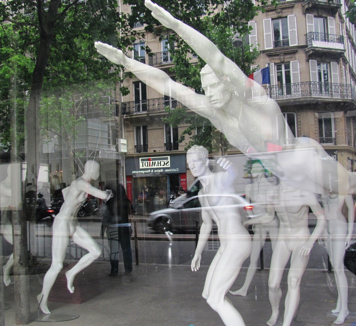 A mostly male group of mannequins cavort in their birthday suits in a Paris shop window.