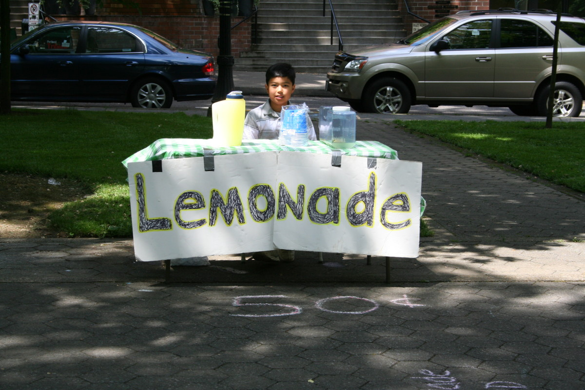 A young entrepreneur selling lemonade at a very affordable price; finding the right price is the key to success.