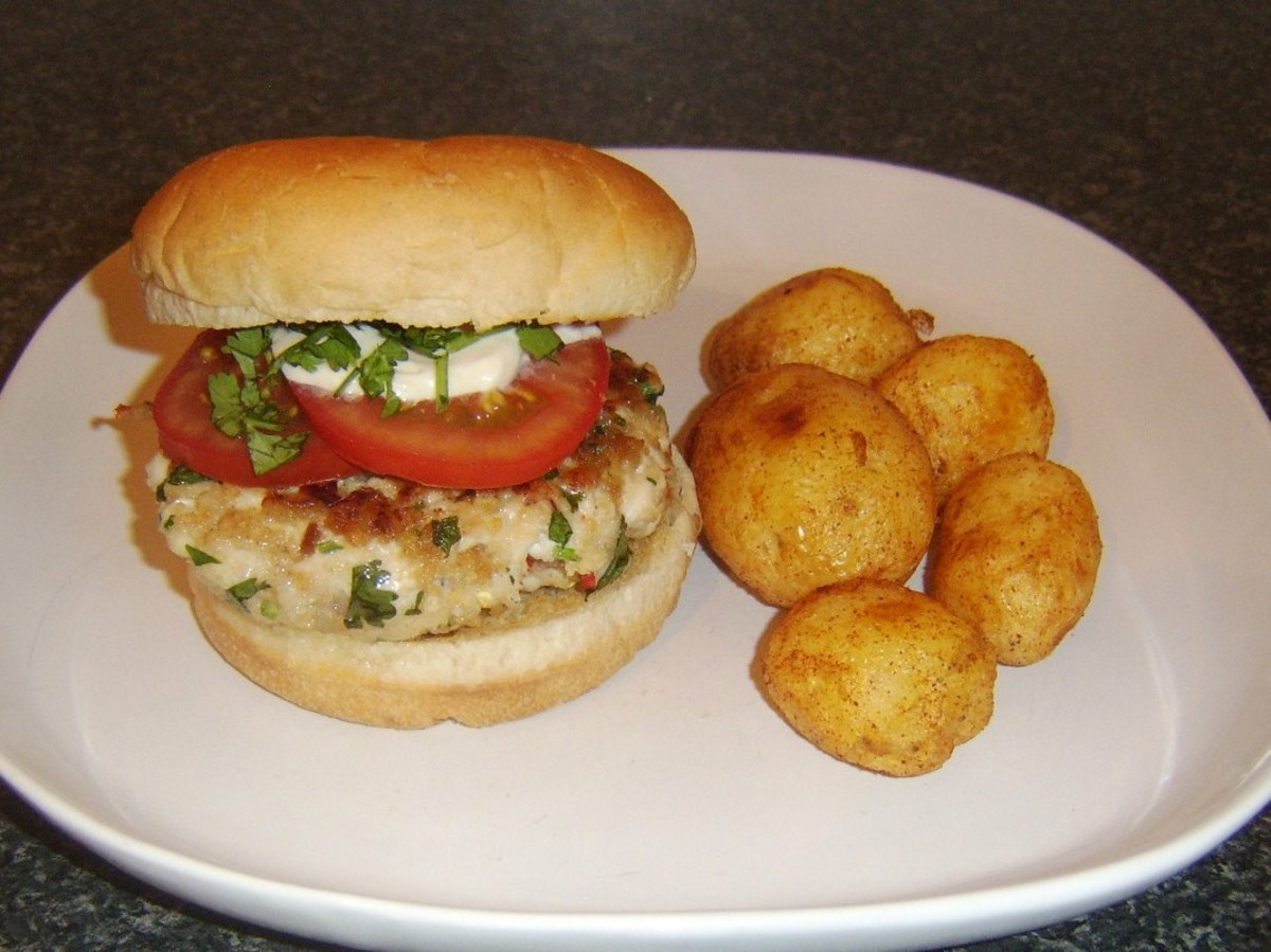 Spicy chicken burger with roast potatoes.