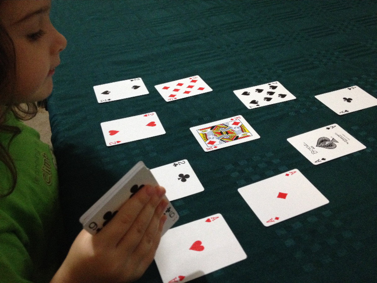 Young girl playing the card game Cricket with cards in a triangle formation