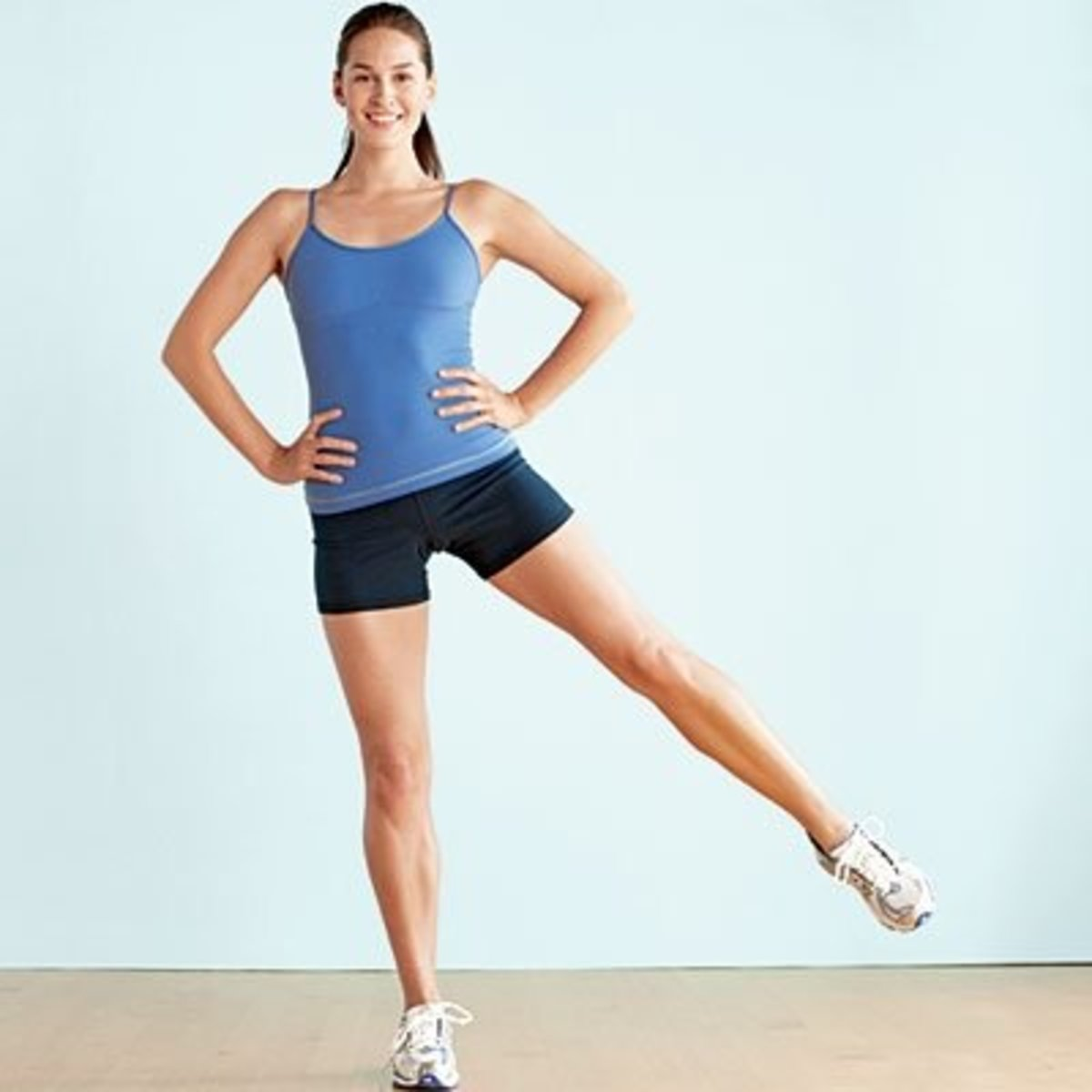 Standing Leg Lift Demonstrated by Pretty Brunette in Blue and Black Fitness Gear