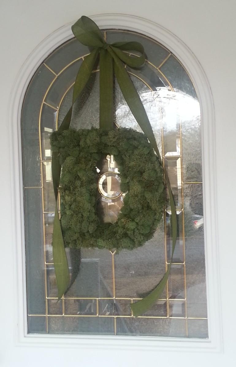 Moss covered monogram wreath hanging on my front door