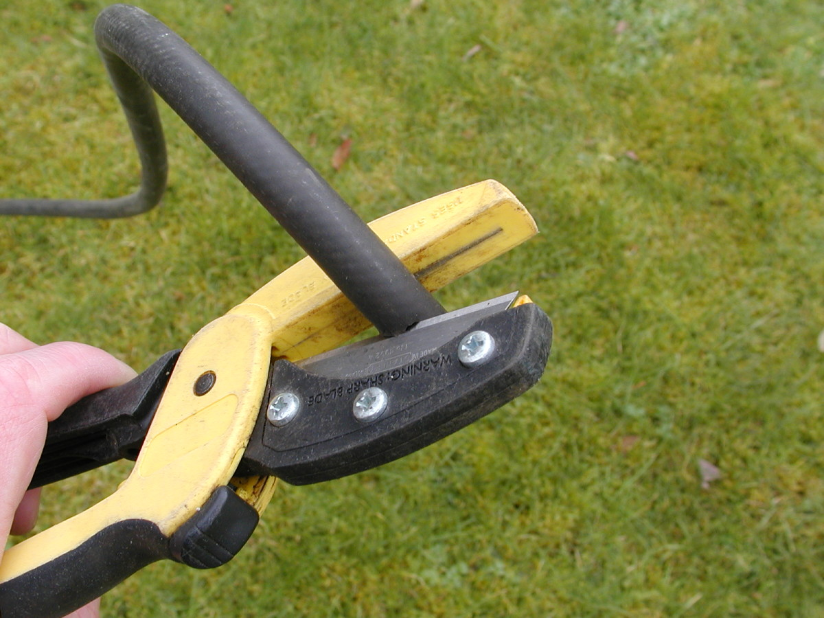"""Cut the end of the hose square. This useful tool for cutting hoses and light pvc tubing is fitted with a widely available """"Stanley"""" type knife blade"""