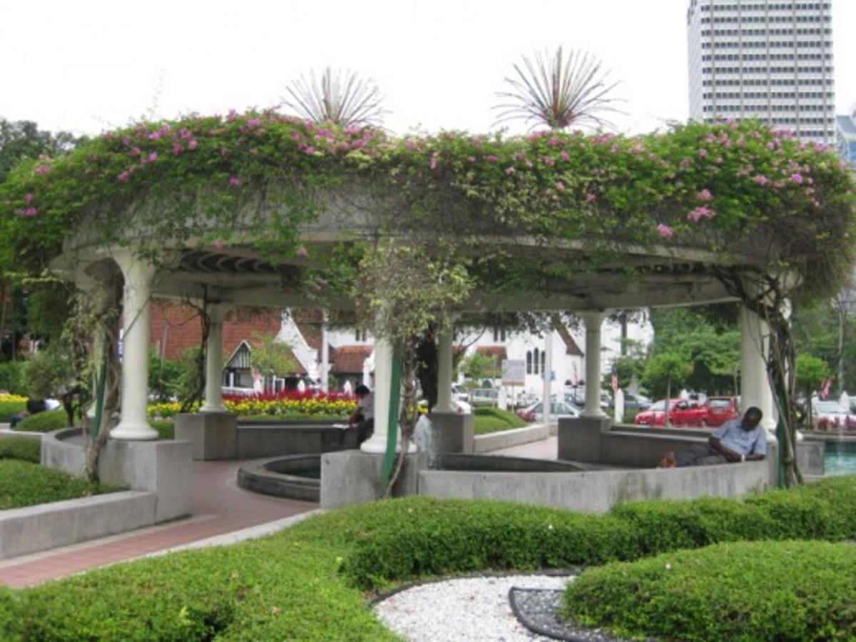 An office worker sleeps near a fountain outside Merdeka Square, Kuala Lumpur.