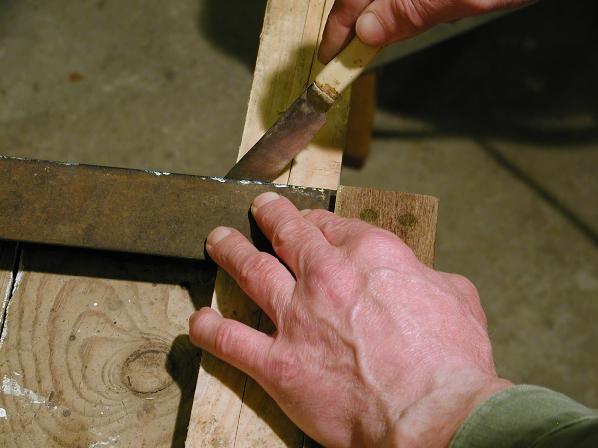 Using a marking knife to mark a section of timber.