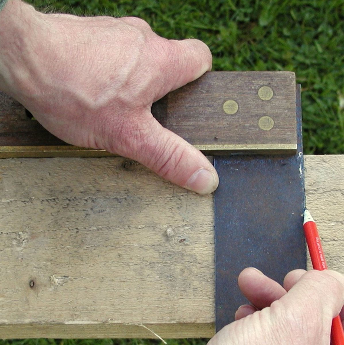 Using a square to mark a 90 degree line as a guide for cutting.