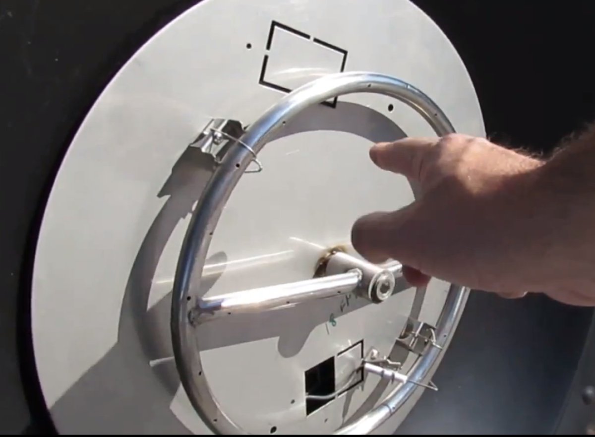 Close up, pointing at flat stainless steel pan with ring burner.