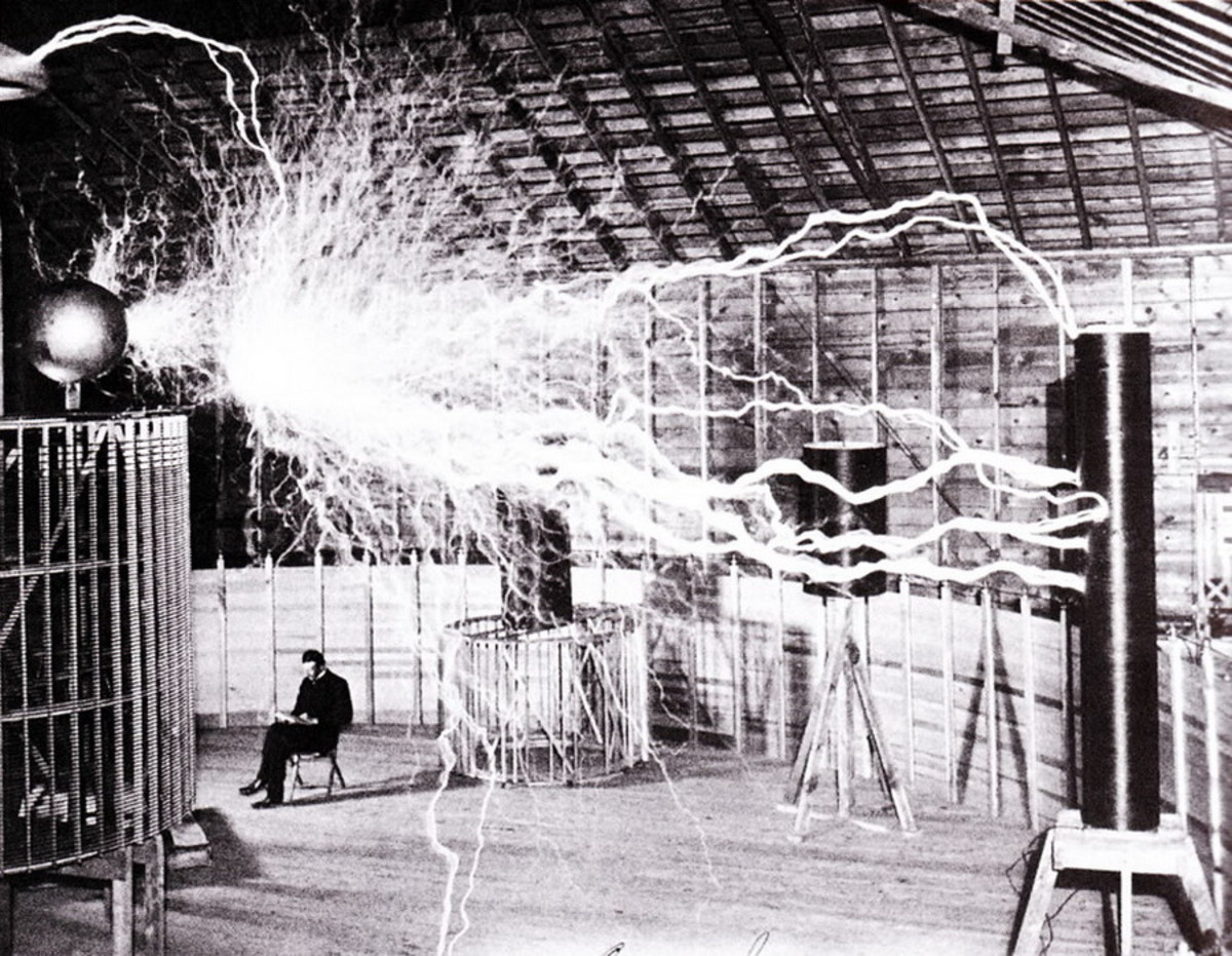 Nikola Tesla basking in his high voltage laboratory.