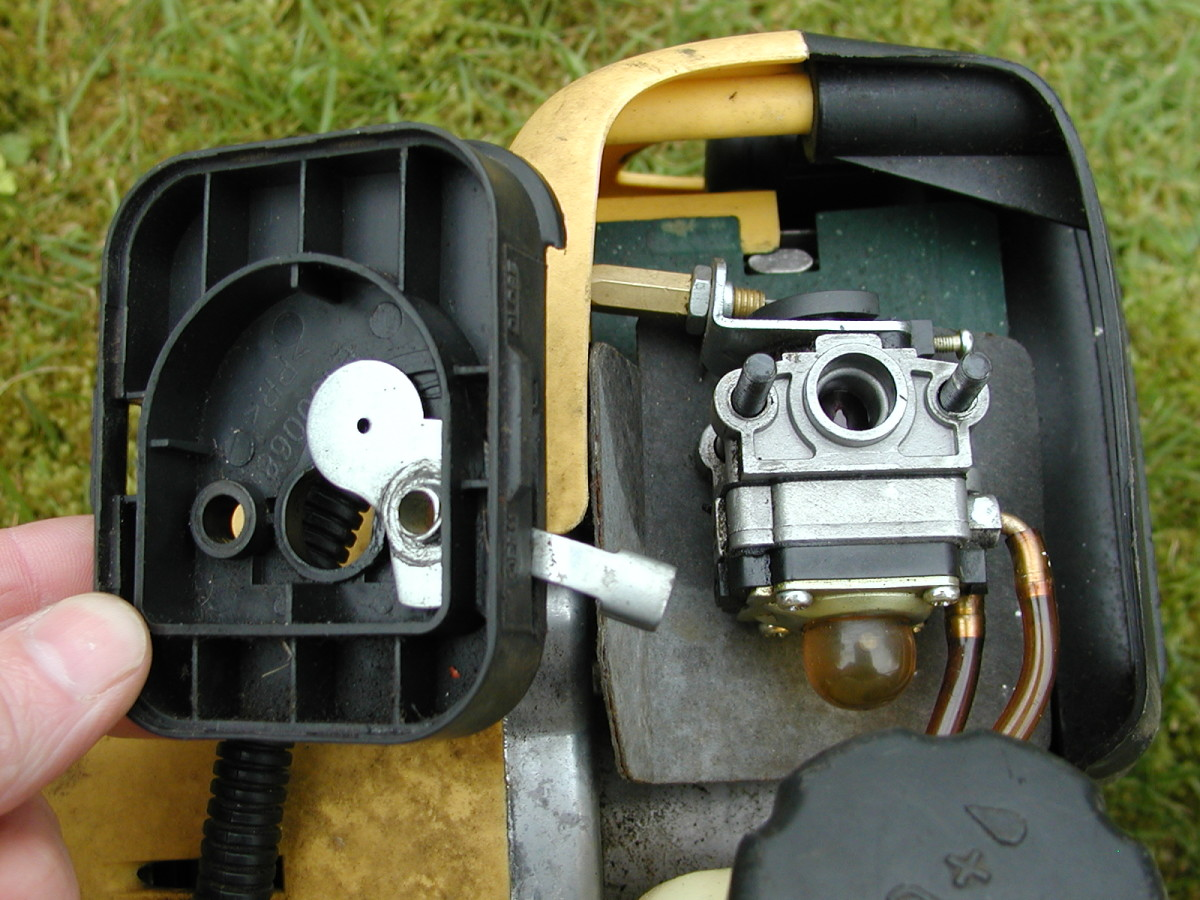 The carburetor exposed: Next, the fuel lines and throttle cable must be removed.