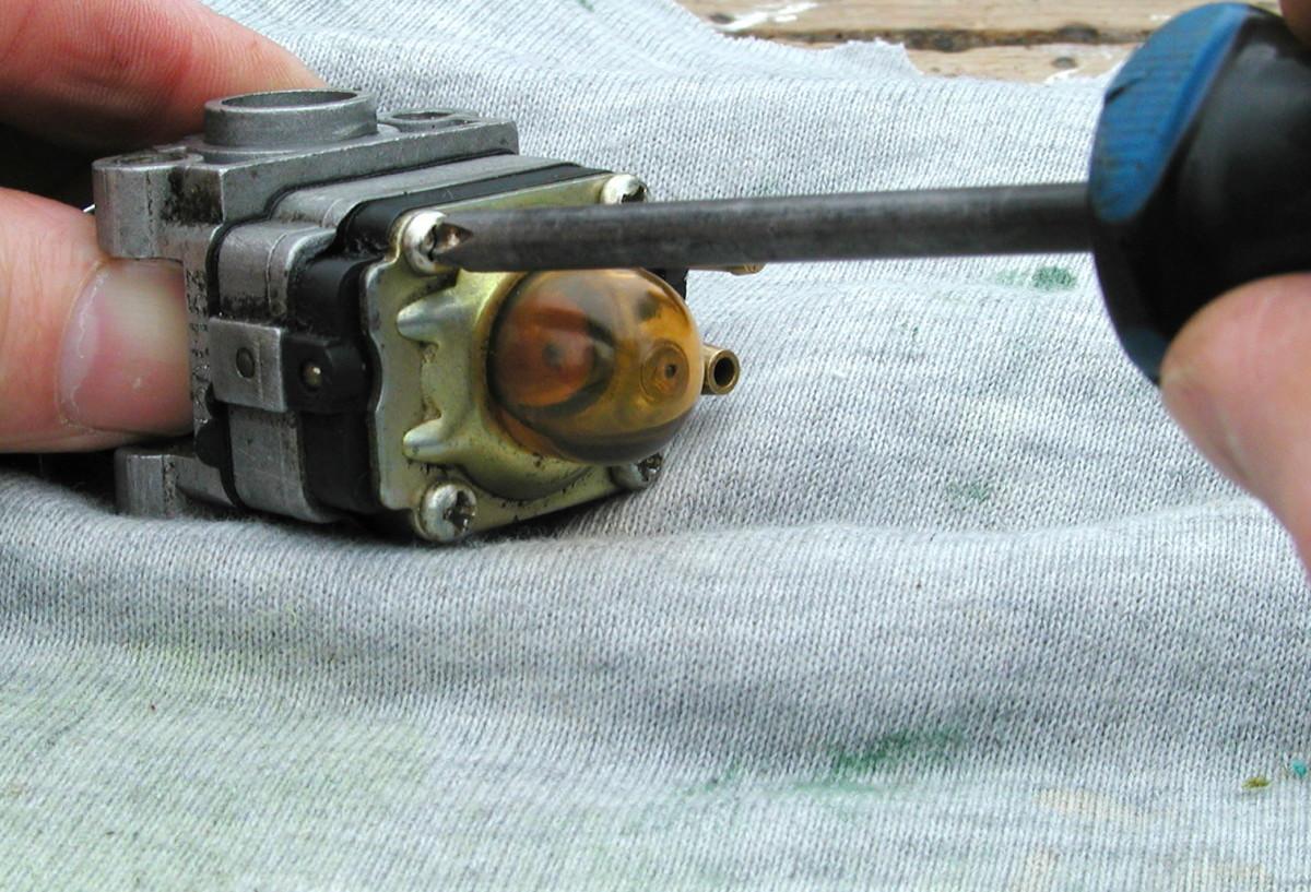 4 screws hold the carburetor together. Remove the primer bulb retaining plate.