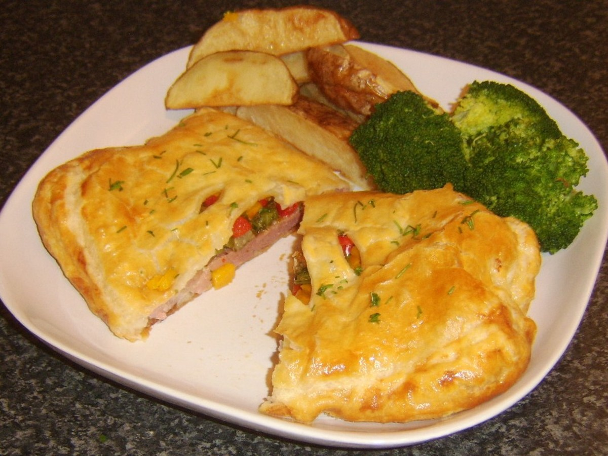 Gammon steak en croute with spicy pineapple stuffing is served with broccoli and deep fried potato wedges