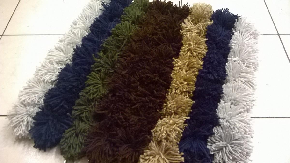 Completed yarn pom pom rug.