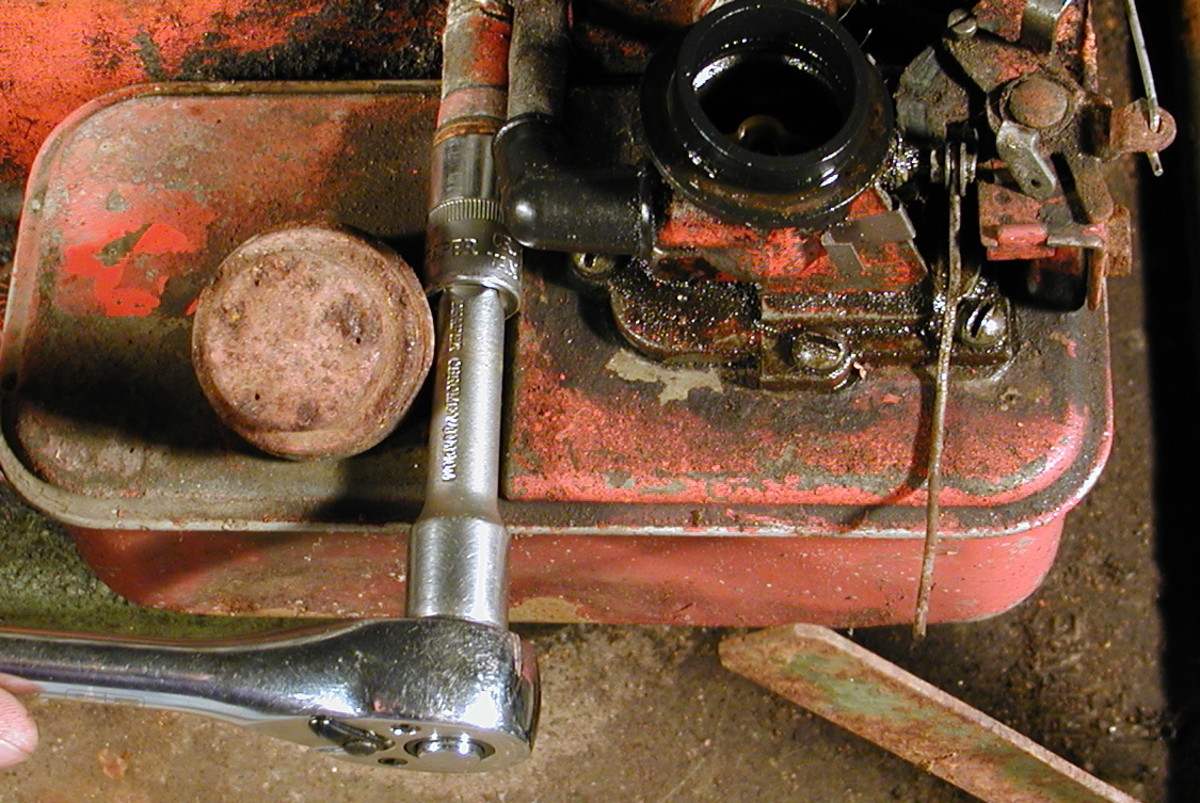 Undo the bolt holding the tank to the engine.