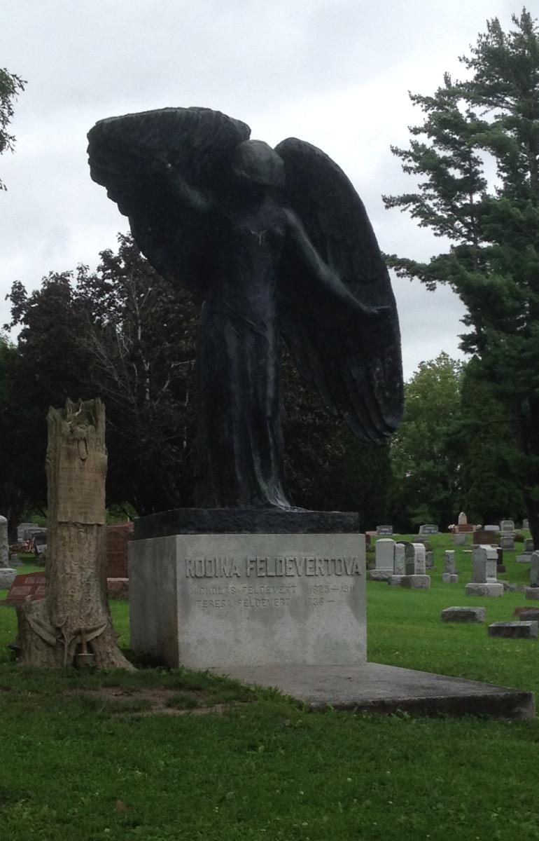 The Black Angel watching over Eddie's tree stump gravestone in Oakland Cemetary